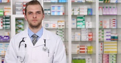 Serious Pharmacist Man Making Hand Gestures Ok Sign in Pharmacy Pan Left Camera Stock Footage