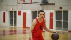 Portrait of a basketball player dribbling the ball on an empty court Stock Footage