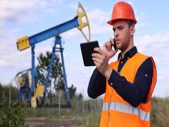 Oil Pump Worker Man Talking Mobile Phone Holding Digital Tablet Resources Field Stock Footage