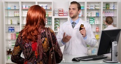 Pharmacist Man Talking with Customer Woman on Drugs Description Pharmacy Store Stock Footage