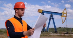 Young Petrochemical Engineer Reading Examine Project Design Plan Layout Oil Pump Stock Footage