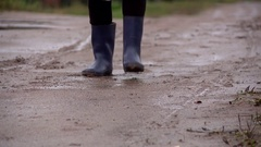 On the bumpy road in the village there is a man in rubber boots Stock Footage