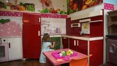 Little girl plays on children's kitchen. Stock Footage