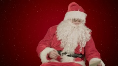 Santa with Christmas letter or wish list on red background with snow Stock Footage