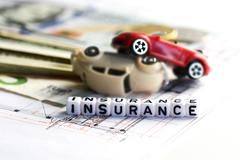 Toy cars accident damage and insurance word from tiled letter blocks Stock Photos