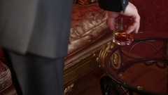 Businessman drinking brandy, puts the glass on the coffee table and irritably Stock Footage