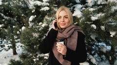 A woman with a glass in forest talking on the phone and smiling Stock Footage