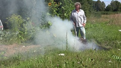 Senior peasant woman burn grass and refuse in fire on meadow in rural village Stock Footage