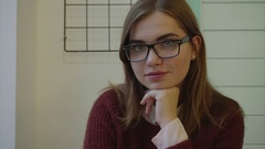 Close-up of young brunette woman in glasses looking at the camera indoors Stock Footage