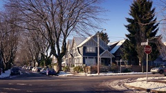 Cars Passing Houses In Snow On Sunny Day Stock Footage