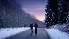 People Walking Through Snowy Woods At Sunset Stock Footage