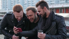 Three handsome young men with beards laughing cheerfully. Good-looking guys Stock Footage