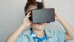 Cute little boy watching video on VR (or Virtual Reality) glasses Stock Footage