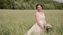 Beautiful smiling bride in a wheat field enjoys her wedding day. Hair and cones Stock Footage
