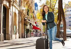 Happy traveler with suitcase on the street Stock Photos