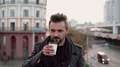 A stylish handsome man with a beard drinking takeaway coffee or tea looking to Stock Footage