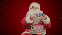 Santa Claus holding a gift in his hand on red background with snow Stock Footage