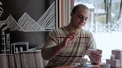 Smiling man talking in a video chat in a cafe. Stock Footage
