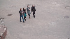View down on the street where four young stylish people walk. Two girls and two Stock Footage