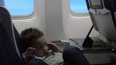 Child entertaining with mobile phone in the plane Stock Footage