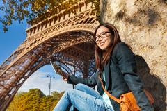 Beautiful young woman taking photo of Eiffel Tower Stock Photos