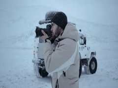A portrait of photographer taking photo in front of Siberian car. Stock Footage