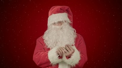 Santa claus reads and sends text messages from his cell phone  on red background Stock Footage