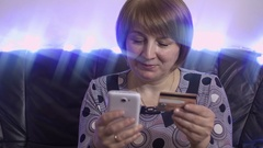 Woman of middle age makes a purchase from a mobile phone by credit card Stock Footage