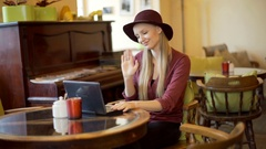 Stylish woman in retro clothes having a videocall on laptop, steadycam shot Stock Footage