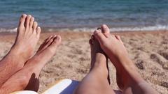 Legs lie on a sun lounger on the beach Stock Footage