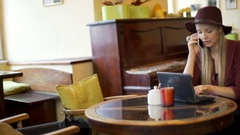 Classic woman chatting on cellphone and using laptop in the cafe, steadycam shot Stock Footage