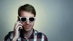Young man in glasses talking on cell phone Stock Footage