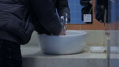 A man washes his hands and face in a public toilet. Stock Footage