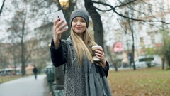 Happy girl in warm clothes doing selfies on smartphone in the autumnal park, ste Stock Footage