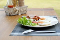Breakfast meal with ham sausage egg and salad Stock Photos