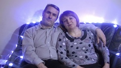 Middle aged couple relaxing on the couch smiling at camera at home in the living Stock Footage