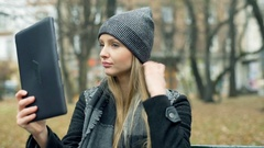 Beautiful girl checking her appearance in a tablet while sitting in the park, st Stock Footage