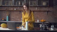 Woman preparing breakfast using computer in apartment Stock Footage