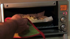 Fish pieces cooking in the hot oven. Someone is opening the oven door and checki Stock Footage
