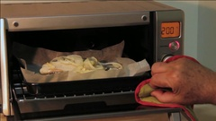 Fish pieces cooking in the hot oven. Someone is opening the oven door and checki Arkistovideo