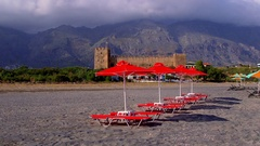 RED SUN BEDS PARASOLS CASTLE FRANGOKASTELLO CRETE Stock Footage