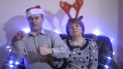 Middle-aged couple wearing santa hat and reindeer horns sitting on a couch and Stock Footage