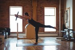 Woman practicing on pilates while standing on one leg Stock Photos