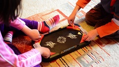 Children playing a game of football on the carpet in their room playing Stock Footage