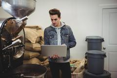 Man using laptop while standing besides coffee grinding machine Stock Photos