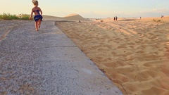 Small Girl Runs Barefooted along Path by Sand Dunes at Sunset Stock Footage