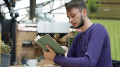 Absorbed boy reading book in the cafe and texting back on smartphone, steadycam  Stock Footage