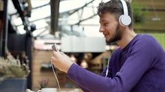 Young man wearing headphones and having a videocall on smartphone, steadycam sho Stock Footage