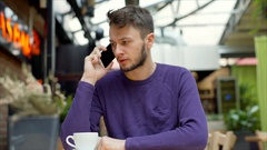 Angry boy sitting in the cafe and having an argument on cellphone, steadycam sho Stock Footage