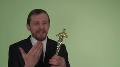 Person receives a statuette on a green background Stock Footage